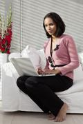 A woman sitting on a sofa using a laptop - stock photo