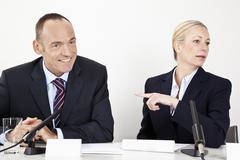 A man and a woman sitting at a desk with microphones Stock Photos