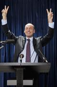 A man in a suit standing at a lectern and gesturing - stock photo