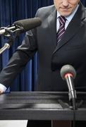 Detail of a man standing at a lectern - stock photo