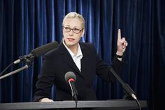 A woman in a suit speaking at a lectern - stock photo