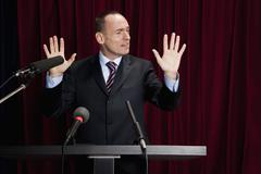 A man in a suit gesturing at a lectern - stock photo