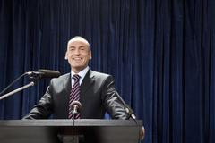 A man in a suit standing at a lectern - stock photo