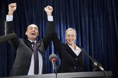 A man and a woman cheering at a lectern - stock photo