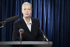 A woman in a suit at a lectern - stock photo