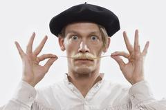 A costumed man twisting his mustache, portrait - stock photo