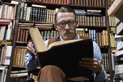 A man reading a book in a bookstore Stock Photos