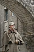 Stock Photo of A man dressed up as Sherlock Holmes standing under a building arch looking away