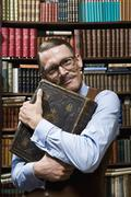 A man holding a book tightly to his chest happily in a bookstore Stock Photos
