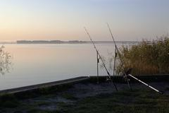 Two fishing rods on an embankment Stock Photos