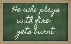 Expression -  he who plays with fire gets burnt - written on a school blackbo Stock Illustration