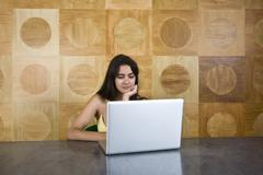 Stock Photo of A young woman sitting at a marble table using a laptop