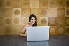 A young woman sitting at a marble table using a laptop Stock Photos