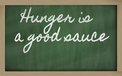 Expression - hunger is a good sauce - written on a school blackboard with cha Stock Illustration