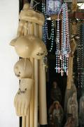 Wax body parts and rosary beads hanging in a store - stock photo