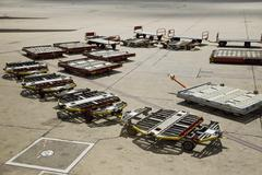 Baggage trailers on an airport tarmac Stock Photos