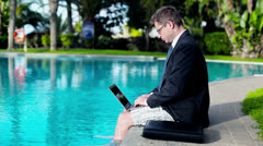 Businessman working with laptop on his vacation by the swimming pool - stock footage