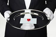 Stock Photo of Midsection of a man in a tuxedo holding a letter on a silver platter