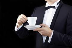 Midsection of a man wearing a tuxedo and holding a cup and saucer Stock Photos