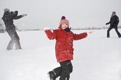 Kaksi vanhemmat ja heidän tyttärensä ottaa lumisota Kuvituskuvat