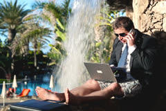 Businessman working by the waterfall on his vacation - stock footage