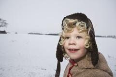 A boy outdoors in winter, head and shoulders, portrait - stock photo