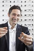 A smiling optician holding up a pair of glasses to the camera in an eyewear - stock photo