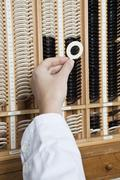 An optometrist selecting a test lens from a case Stock Photos