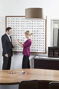An optician holding up glasses to a man in an eyewear store Stock Photos