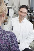 An ophthalmologist doing a slit-lamp biomicroscope exam on a patient - stock photo