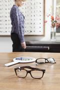 Two pairs of glasses (one in focus) in an eyewear store, woman in background - stock photo