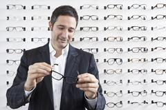 Stock Photo of A mature man choosing a pair of eyeglasses in an eyewear store