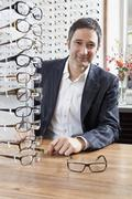 A mature man choosing a pair of eyeglasses in an eyewear store - stock photo
