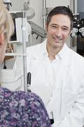 An ophthalmologist using a slit-lamp biomicroscope to examine a patient - stock photo
