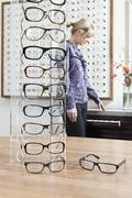 An eyeglasses display in an eyewear store and a woman shopping in background - stock photo