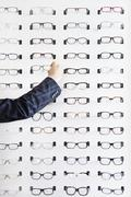 A human hand choosing a pair of glasses in an eyewear store - stock photo