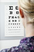A woman reading an eye chart, over the shoulder view Stock Photos