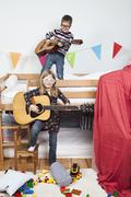 Two children playing with guitars in a child's playroom Stock Photos