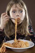 Stock Photo of A young girl eating spaghetti messily, studio shot