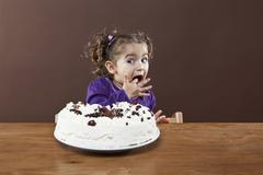 A young girl sneaking a taste of a frosted cake, studio shot Stock Photos