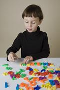A boy playing with letter magnets Stock Photos