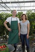 A man and a woman standing together in a greenhouse Stock Photos
