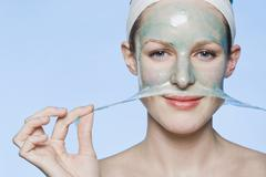 A woman peeling a face mask off her face - stock photo