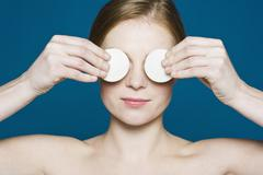A woman with two cotton pads held up over her eyes - stock photo