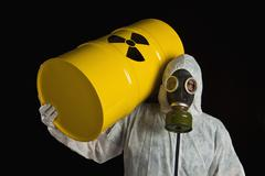 A Person Carrying A Radioactive Barrel And Wearing Protective Clothing - stock photo