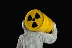 A Person Carrying A Radioactive Barrel - stock photo