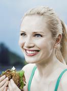 A woman eating a sandwich on 7-grain bread Stock Photos