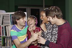 Four friends celebrating with confetti and champagne - stock photo