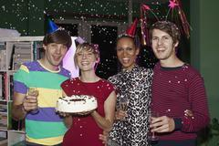 Four friends celebrating with confetti, champagne and cake - stock photo