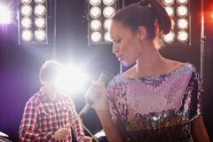 A woman singer accompanied by a man on drums performing on stage Stock Photos